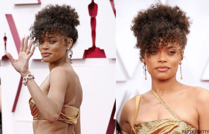 Andra Day wearing long earrings, diamond bracelet, and a gold outfit at 2021 Oscars