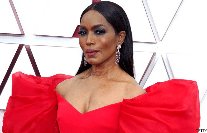 Angela Basset wearing long earrings and a red dress at the 2021 Oscars