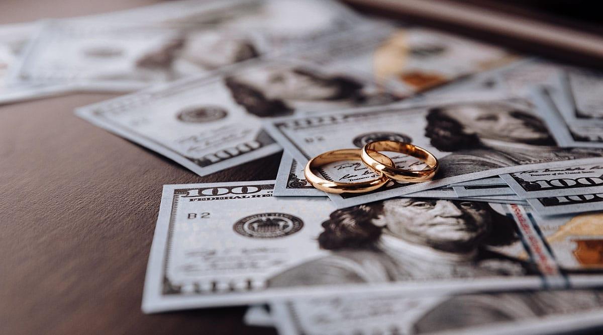 Wedding rings on hundred-dollar bills